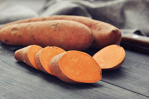 photo of raw sweet potatoes on wooden background closeup