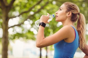 photo of woman jogger in the park drinking water